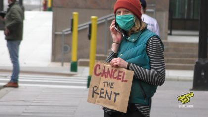 """Masked person on the phone holds """"cancel the rent"""" sign"""