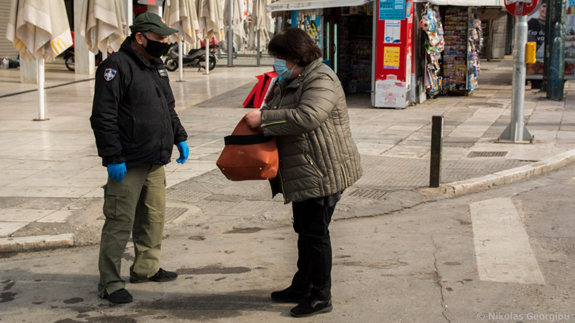 Woman has her movement papers checked in Athens, Greece