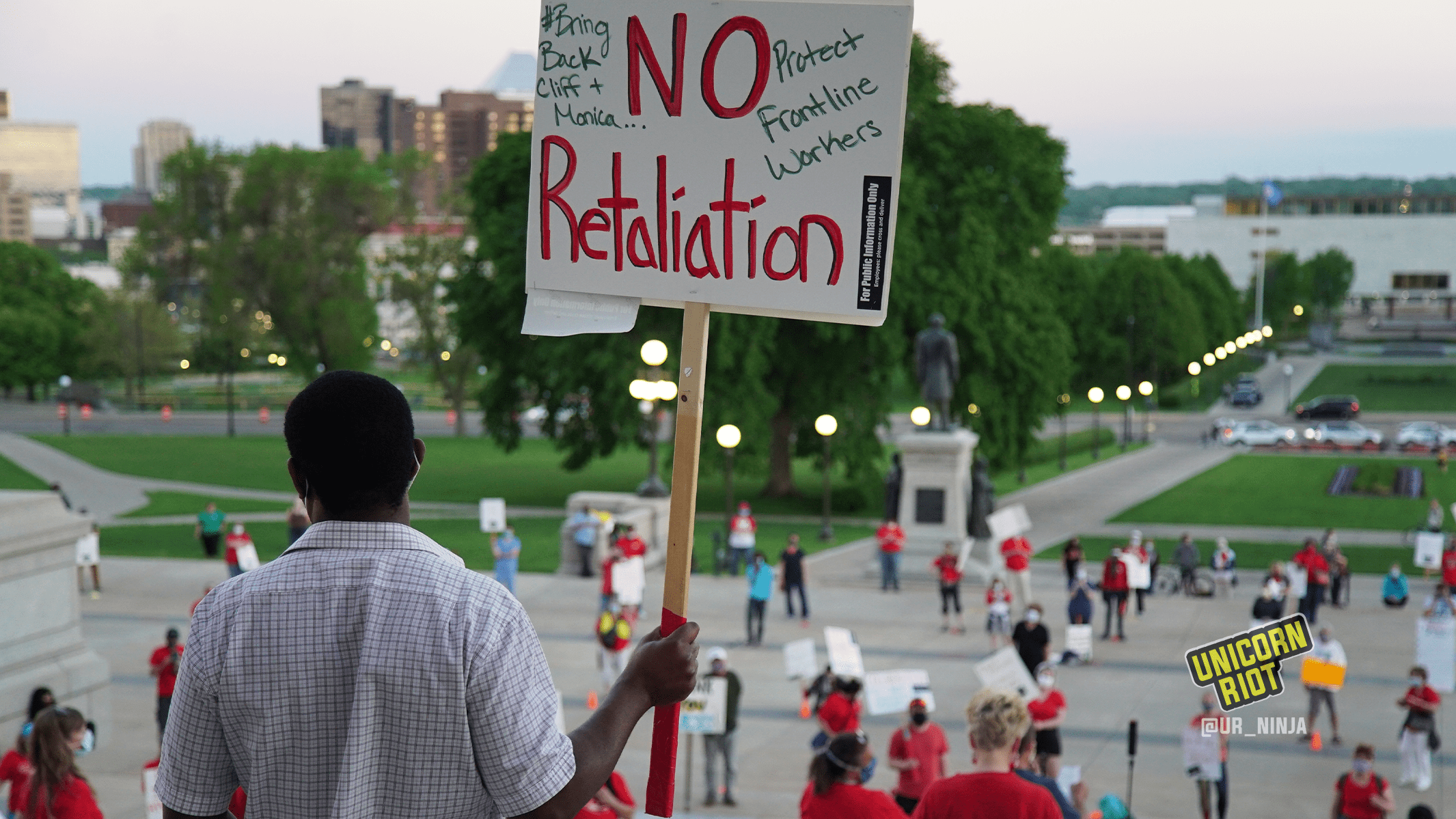 "image: a protester stands in front of the entrance to the Minnesota state capitol facing the crowd of protesters, who are spaced out physically-distanced from one another by small orange cones. The protester is holding a sign, ""NO retaliation, #BringBackCliffAndMonica, Protect Frontline Workers"""