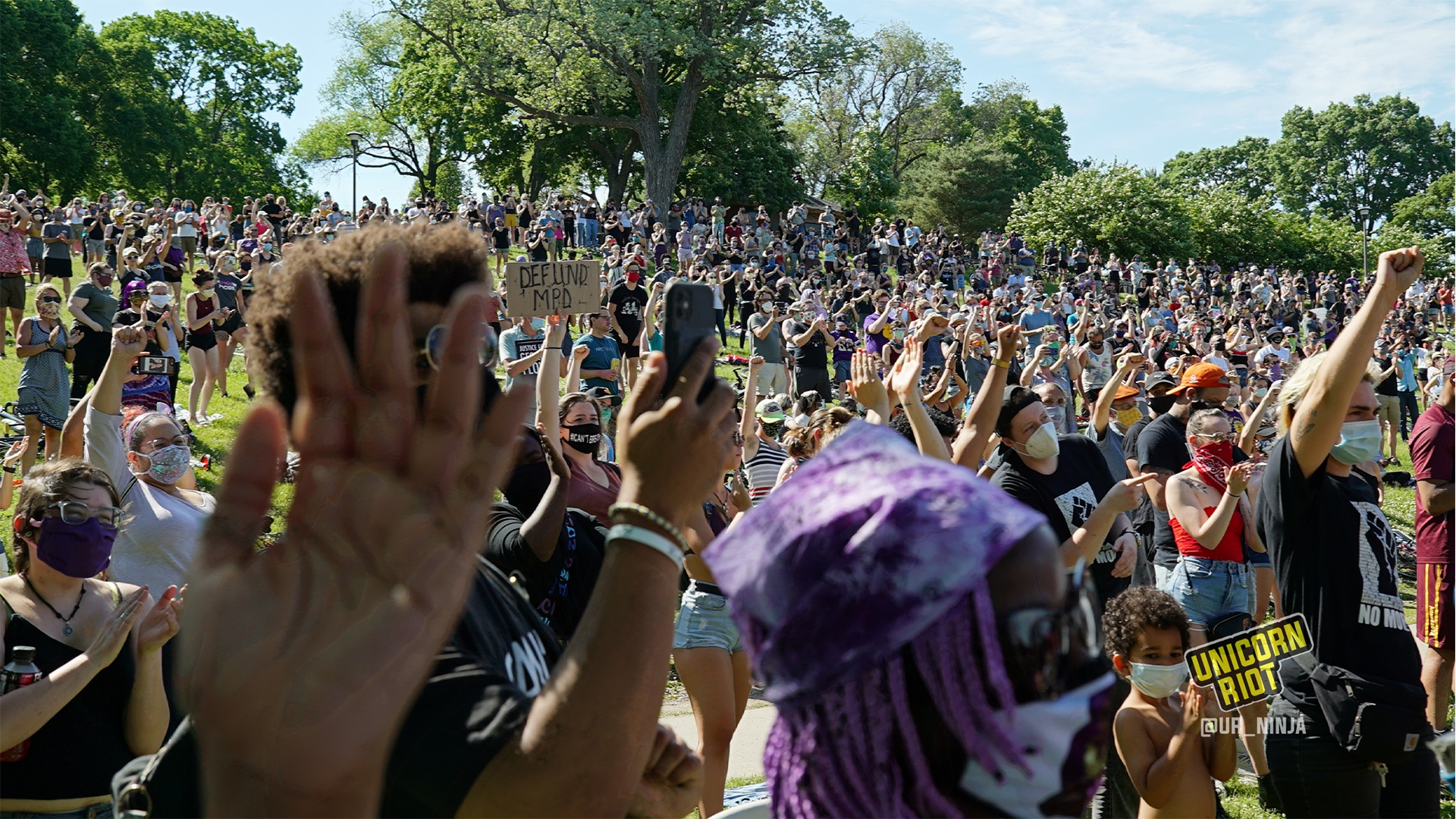 image: the hill of protesters reacts positively to the notion of defunding & disbanding the Minneapolis police department. In the foreground one person's left hand is upraised with their fingers outstretched and their palm towards the stage.