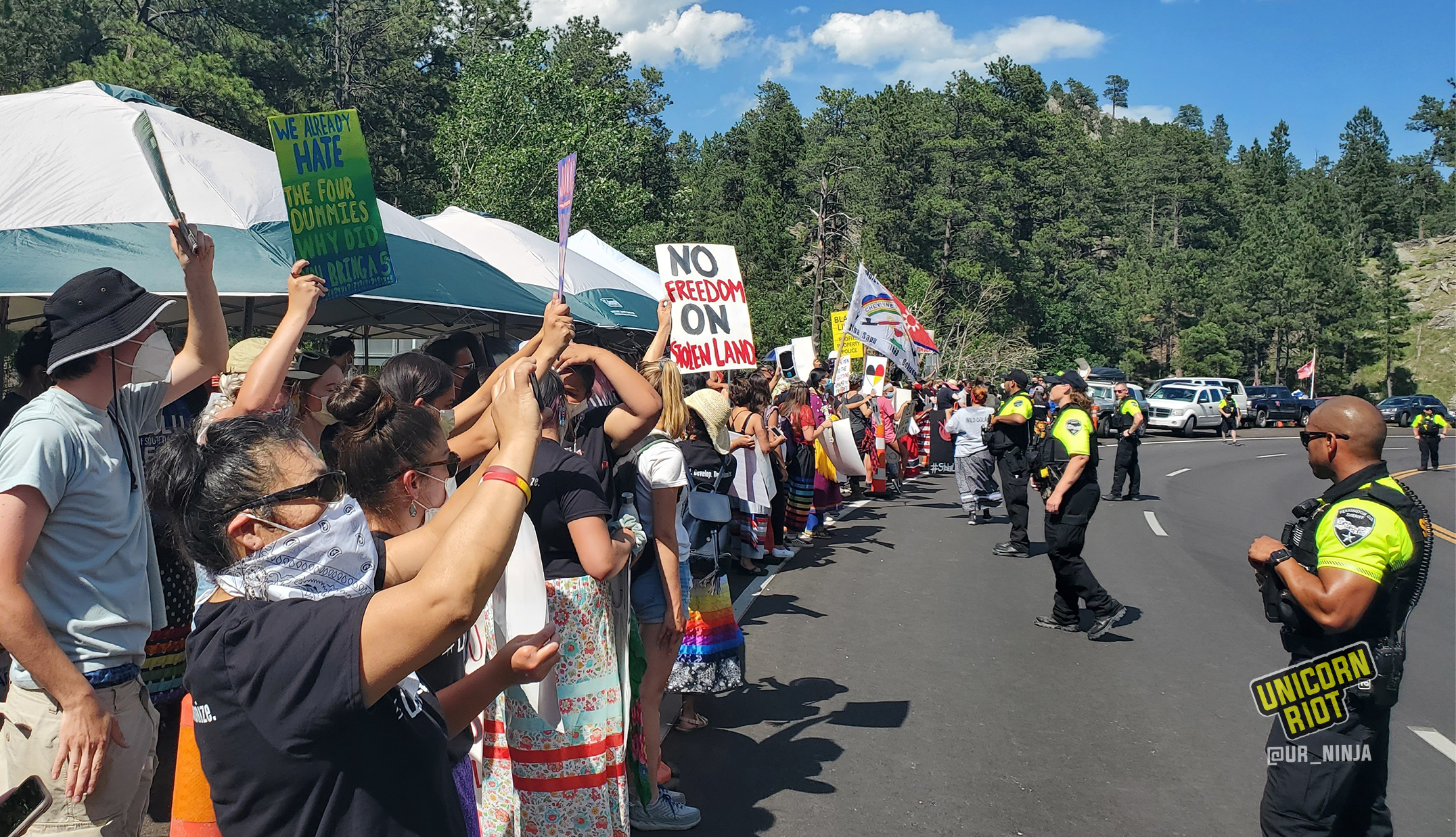 """image: Indigenous people and activists gathered on the side of the road leading to Keystone, SD. The anti-Trump, anti-Mount Rushmore demonstrators hold protests signs such as """"We already hate the four dummies, why did you bring a 5th?"""""""