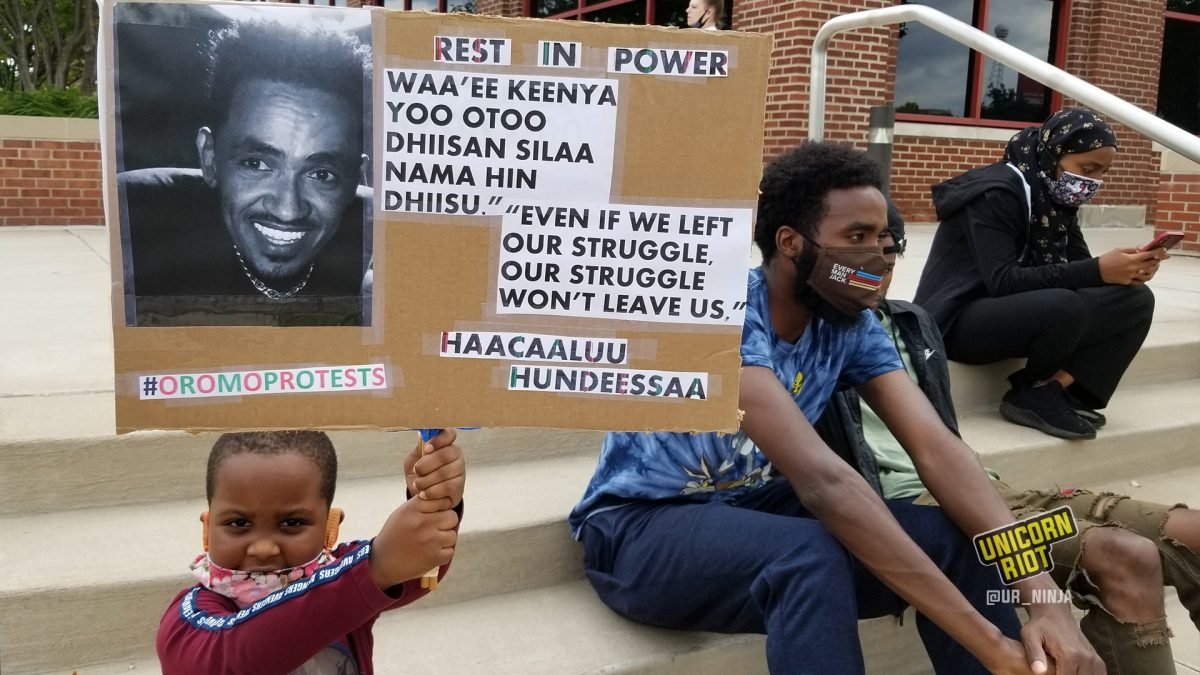 Very young child holds Rest in Power Hundessa sign