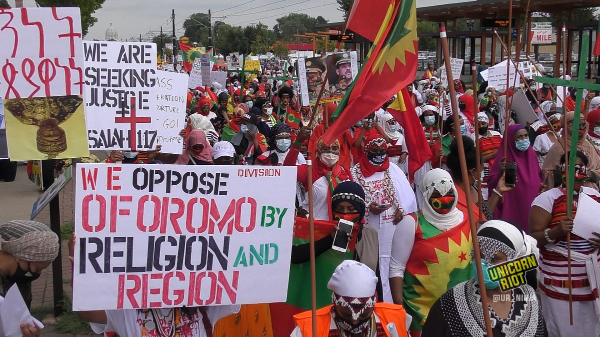 """Sign reads """"We oppose division of Oromo by religion and region"""" at the women's march on August 7, 2020 in Saint Paul, MN"""
