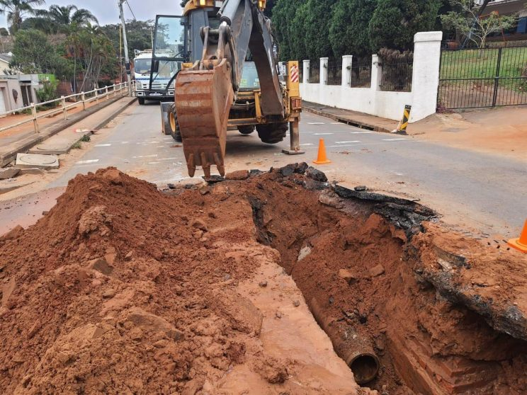 Excavator digs around water pipe on road