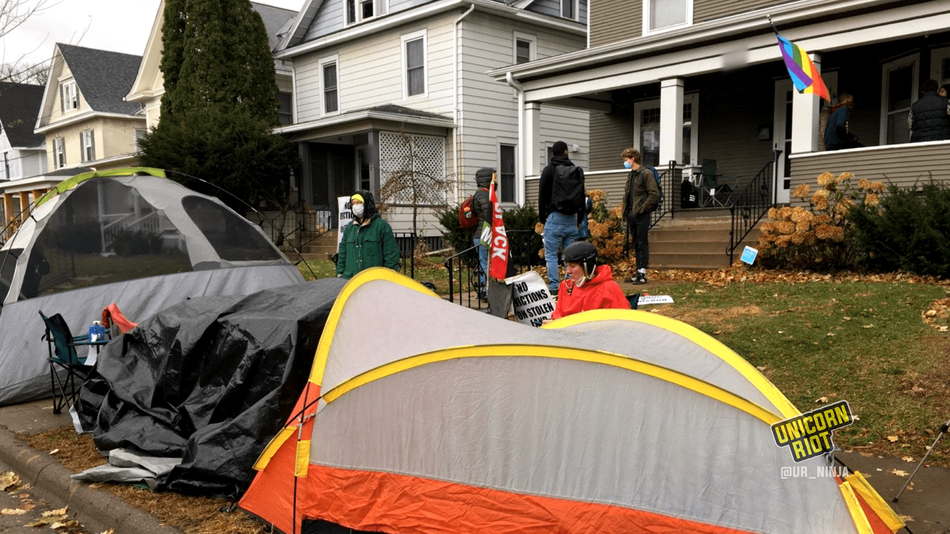 image: single- and double-person tents are positioned on the sidewalk in front of Commissioner Marion Greene's home in South Minneapolis. 5 community members are gathered on her front lawn talking, while a few others are sitting at a table on her front porch.